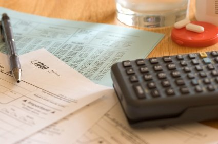 irs tax relief woman at table with 1099-C and 1040 tax forms